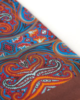 Angled closer view of the copper-brown silk scarf with focus on the large, ornate patterns in blue, orange, white and red.