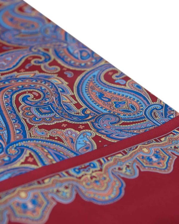 Angled view of the blue paisley patterns complemented with pink, lilac and cream accents on the red-maroon coloured scarf, leading with the elegant border.