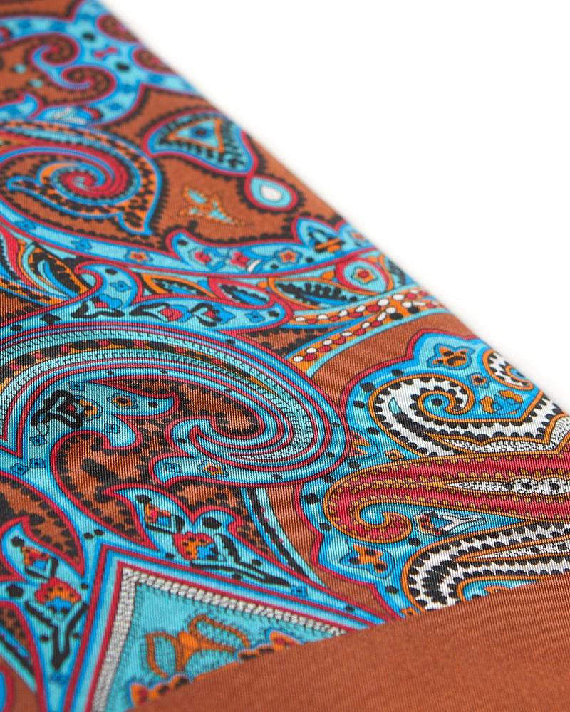 Angled view of the brown fabric with blue and red patterns highlighted with white, black and orange accents.