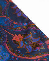 Angled closer view of the navy-blue silk scarf with focus on the ornate purple, orange, pink and black paisley patterns.