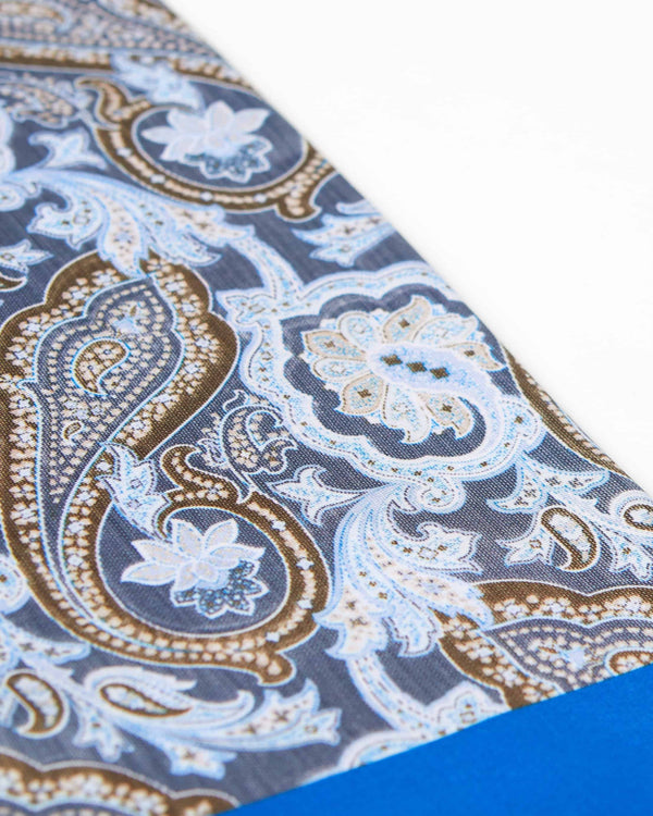 Angled view of the large, low-key paisley patterns on the beautiful grey-blue scarf.
