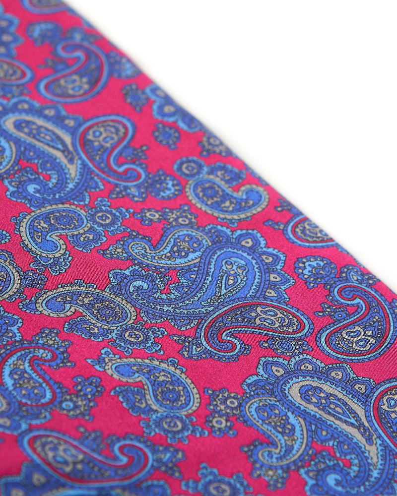Angled view of the bright pink-red fabric with blue paisley patterns highlighted with pale grey accents.