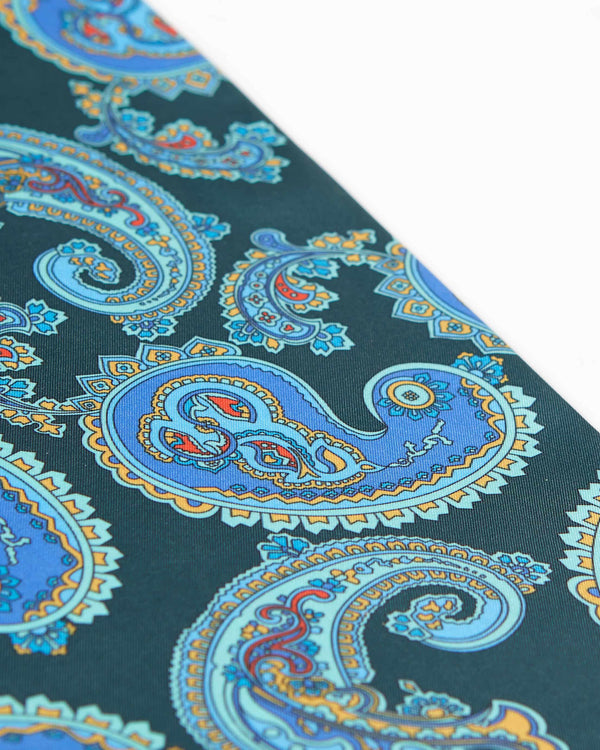 Angled view of the blue paisley patterns complemented with orange and red highlights on the sea green coloured scarf.
