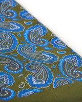 Angled closer view of the dark green silk scarf with focus on the blue paisley patterns.