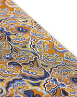 Angled view of the scarf, focussing on a segment of the paisley-inspired patterns in blue, orange, yellow, black and white.
