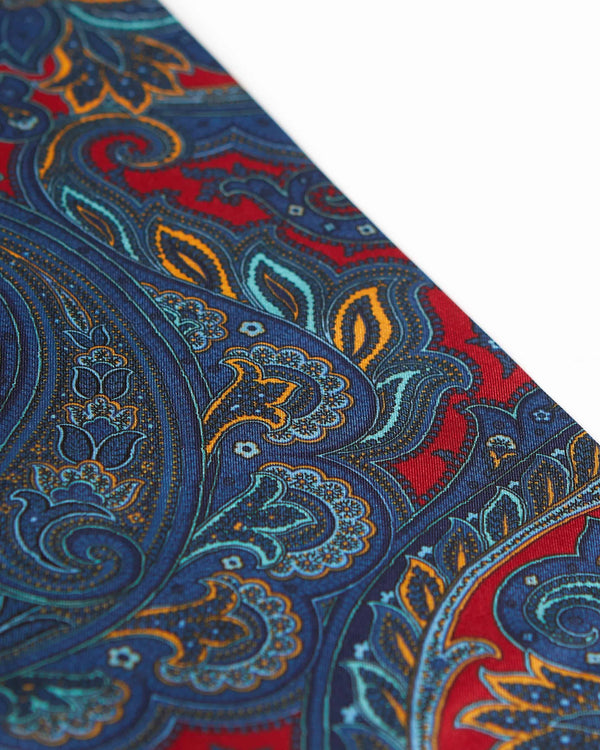 Angled view of the light and dark blue, orange and grey paisley patterns on the deep red scarf.
