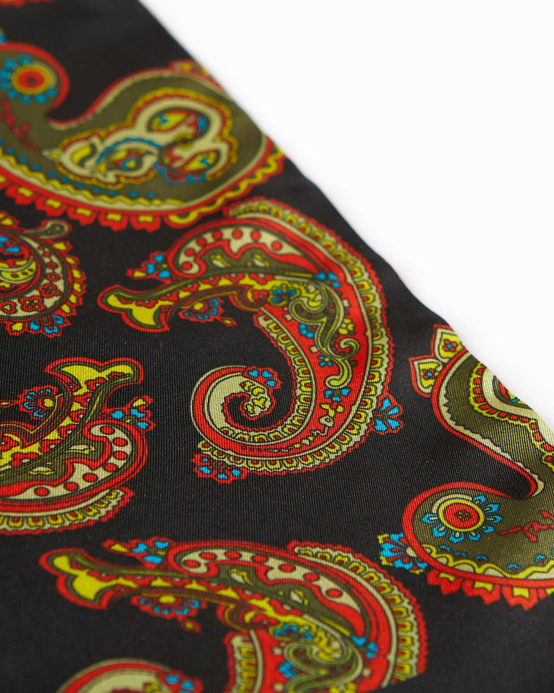 Angled closer view of the black silk scarf with focus on the ornate multi-coloured paisley patterns.
