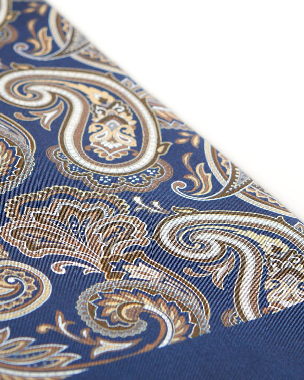 Angled view of the elegant navy blue and gold patterned 100 percent silk scarf, presenting a closer view of the big golden paisley patterns.