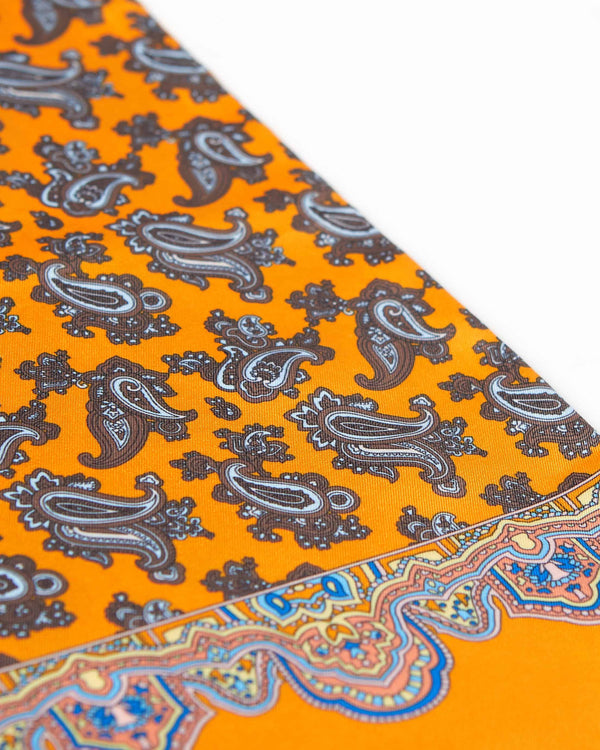 Angled view of the patterned scarf, focussing on the contrasting multi-coloured border and brown paisley patterns.