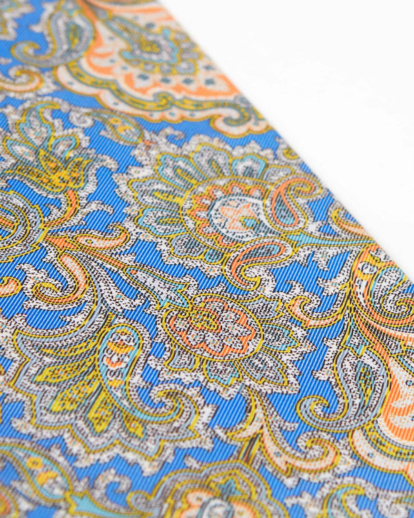 Angled view of paisley patterned scarf, focussing on the multicoloured decorative patterns on a sky-blue background.