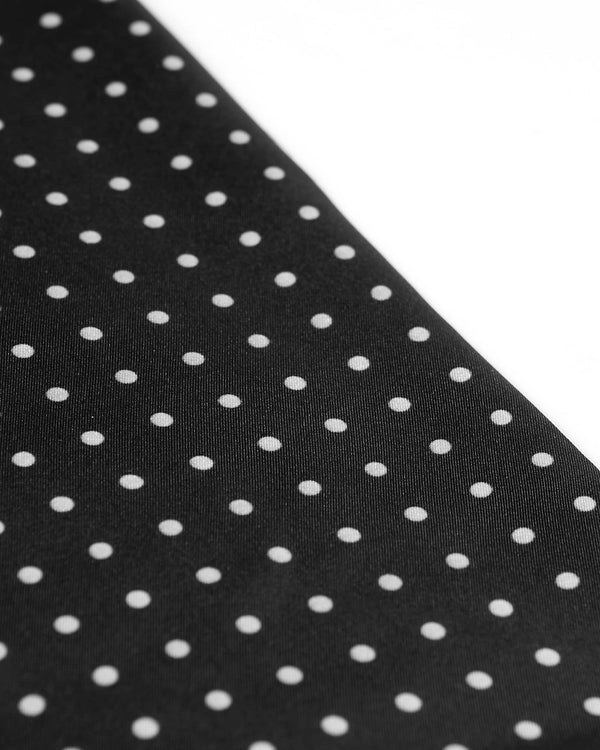 Angled view of the black and white polka dot scarf.