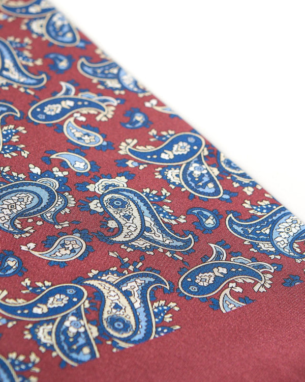 Angled view of the burgundy and blue patterned 100 percent silk scarf, presenting a closer view of the royal-blue and cream paisley patterns.