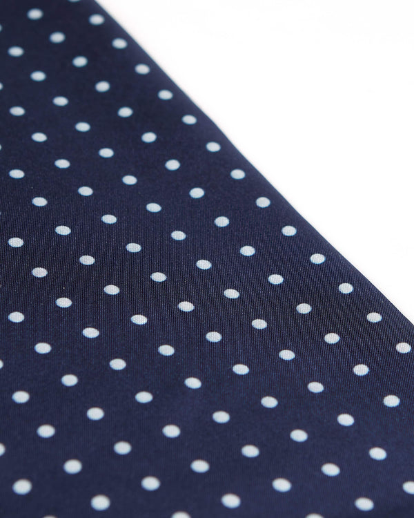 Angled view of the dark blue and white polka dot scarf.
