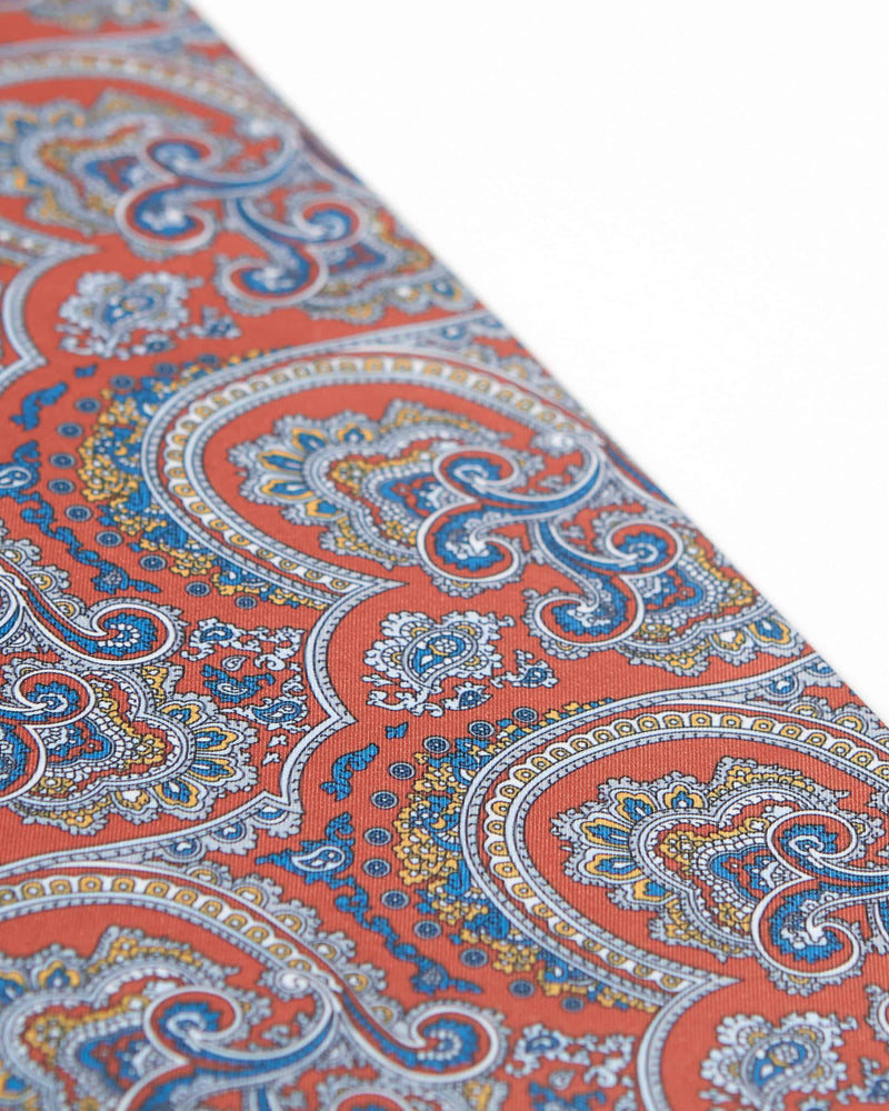 Angled view of the red scarf, highlighting the detailing of the blue and gold paisley inspired patterns.