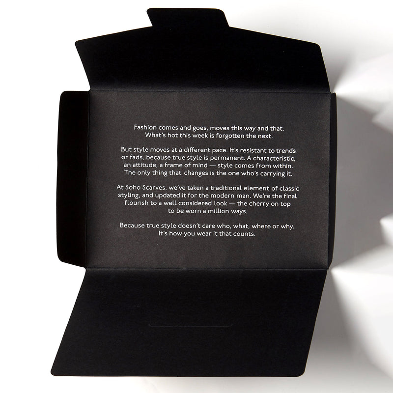 Branded black gift box from Soho Scarves with a closed, re-sealable flap. The gift box is sitting horizontally on a bright white background.
