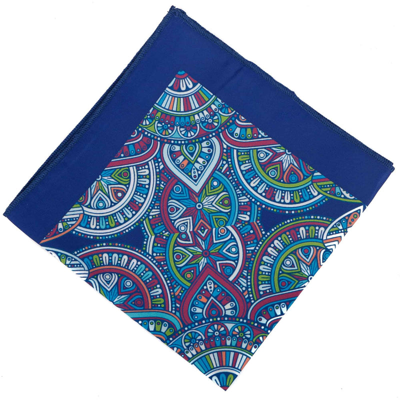 Flat view of the 'Hatsudai' blue pocket square arranged in a diamond shape, clearly showing the solid mid-blue border, hand rolled ends and kaleidoscopic patterns.