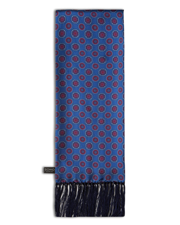 'The Bellevue Aviator' blue silk scarf with small circular and floral-inspired patterns in red and maroon, with white and dark grey highlights. Scarf arranged in a rectangular shape, clearly showing the dark-blue 3-inch fringe and the 'Soho Scarves' label on the left edge.