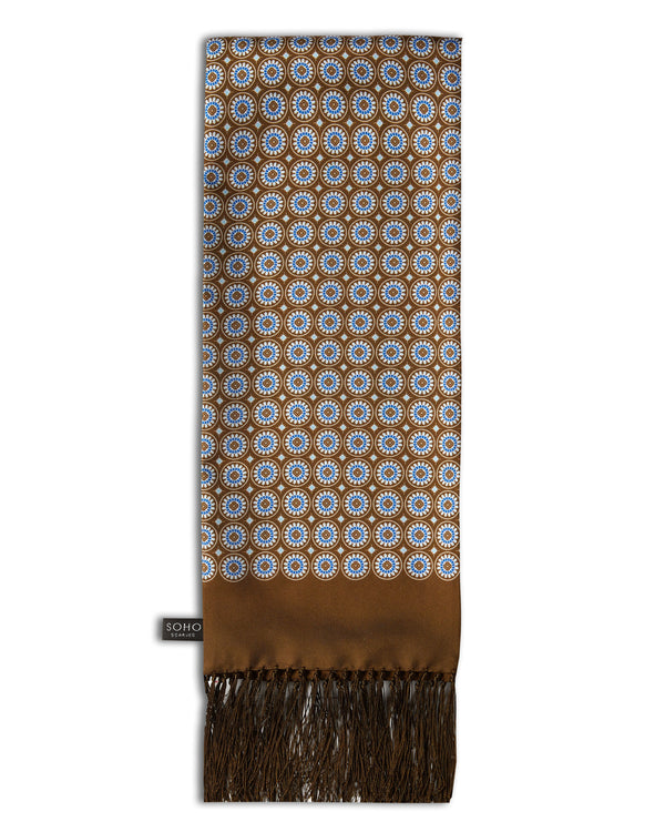 'The Bellingham Aviator' brown silk scarf with small, circular, floral-inspired and diamond patterns in white and blue. Scarf arranged in a rectangular shape, clearly showing the rich-brown 3-inch fringe and the 'Soho Scarves' label on the left edge.