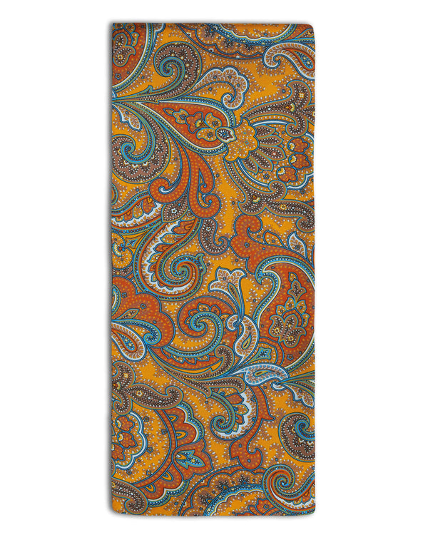 'The Carnaby' paisley patterned silk scarf arranged in a rectangular shape, showing the vibrant yellow fabric with deep orange, cyan and brown patterns and the 'Soho Scarves' branding label attached to the bottom left edge.