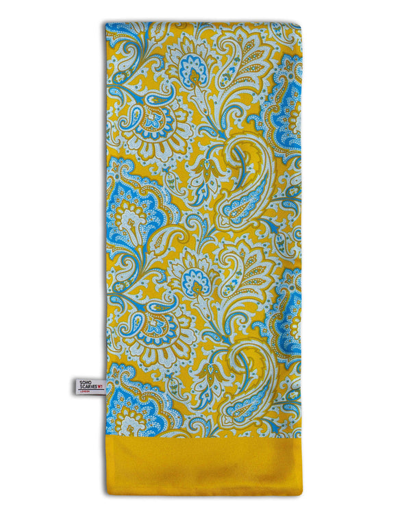 'The Compton Wool' wool backed scarf arranged in a rectangular shape, clearly showing the multi-coloured paisley patterns, golden yellow border and the 'Soho Scarves' label on the left edge.