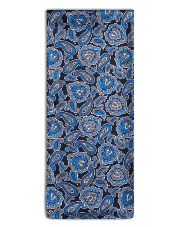 'The DeZon' polyester paisley scarf folded in a rectangular shape showing navy blue fabric with blue paisley and the 'Soho Scarves' label on the left edge.