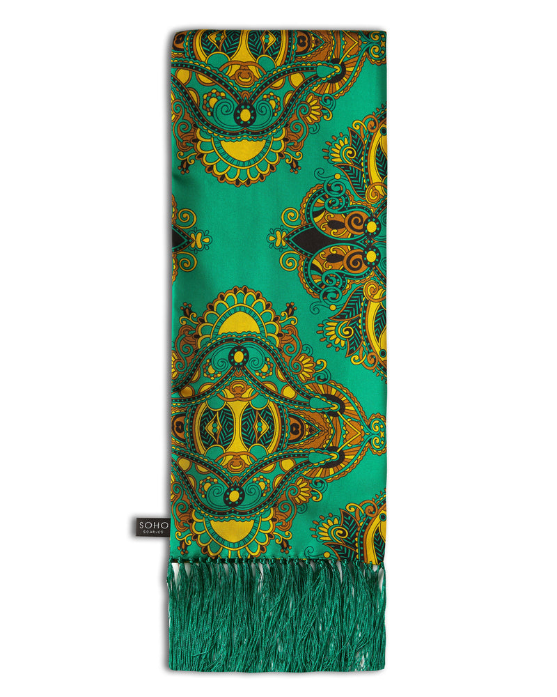 'The Forks Aviator' emerald-green silk scarf with large, paisley-inspired gold patterns, arranged in a rectangular shape, clearly showing the green 3-inch fringe and the 'Soho Scarves' label on the left edge.