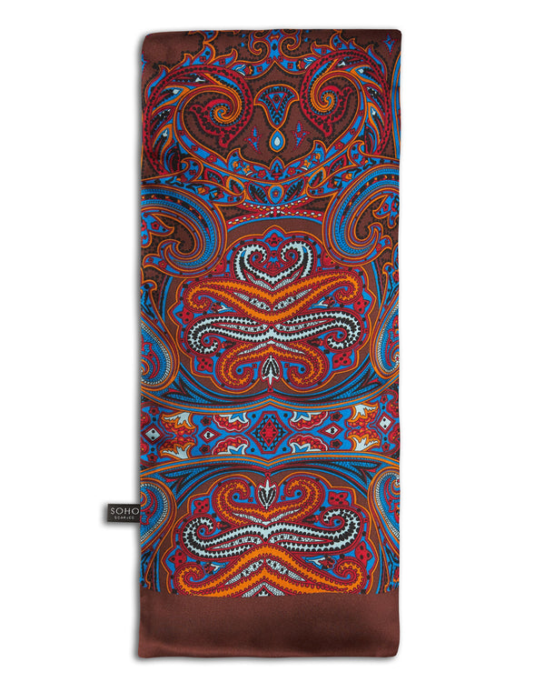 'The Fresco' brown, wool-backed scarf arranged in a rectangular shape, clearly showing the large, paisley-inspired patterns in mid-blue, black, orange, white and red, with the 'Soho Scarves' label on the left edge.