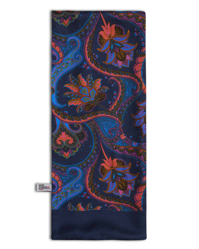 'The Kemp' wool backed scarf arranged in a rectangular shape, clearly showing the multi-coloured paisley patterns, navy blue border and the 'Soho Scarves' label on the left edge.