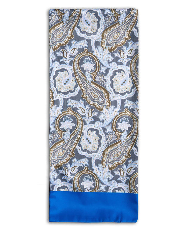 'The King' pale coloured paisley polyester scarf arranged in a rectangular shape. Showing the bright blue fabric border, large paisley patterns and the 'Soho Scarves' label on the bottom-left edge.