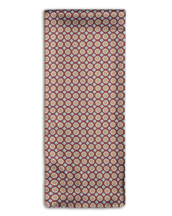 'The Koenji' geometric patterned polyester scarf arranged in a rectangular shape, clearly showing the burgundy fabric with diamond and disc patterns, and the 'Soho Scarves' branding label on the bottom left edge.