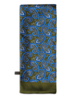 'The Malibu' dark green, wool-backed scarf arranged in a rectangular shape, clearly showing the large, blue paisley patterns with the 'Soho Scarves' label on the left edge.