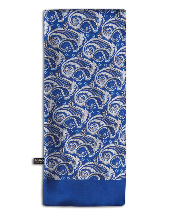 'The Renton' blue, wool-backed scarf arranged in a rectangular shape, clearly showing the silver, black and light blue paisley patterns, and the 'Soho Scarves' label on the left edge.