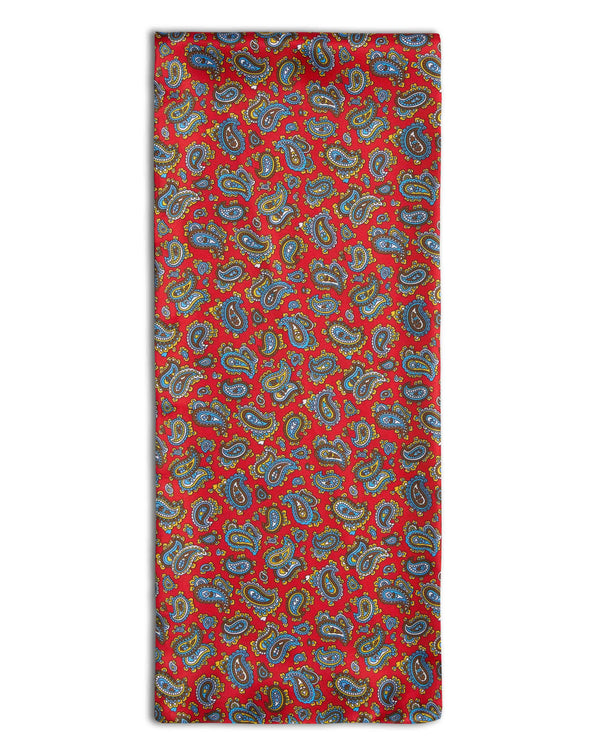 'The Shinjuku' paisley patterned silk scarf arranged in a rectangular shape, showing the deep red fabric with small, multicoloured paisley patterns and the 'Soho Scarves' branding label attached to the bottom left edge.