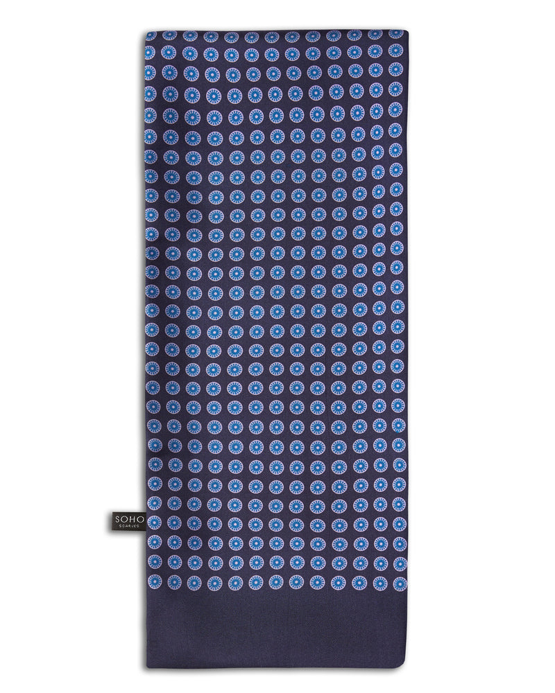 'The Skytree' geometric patterned silk scarf arranged in a rectangular shape, clearly showing the navy-blue fabric with light-blue regular, circular patterns and the 'Soho Scarves' branding label on the bottom left edge.