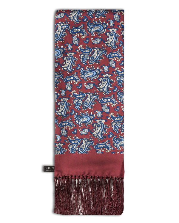 'The Vancouver Aviator' burgundy silk scarf with royal blue and cream paisley patterns, arranged in a rectangular shape, clearly showing the deep-burgundy 3-inch fringe and the 'Soho Scarves' label on the left edge.