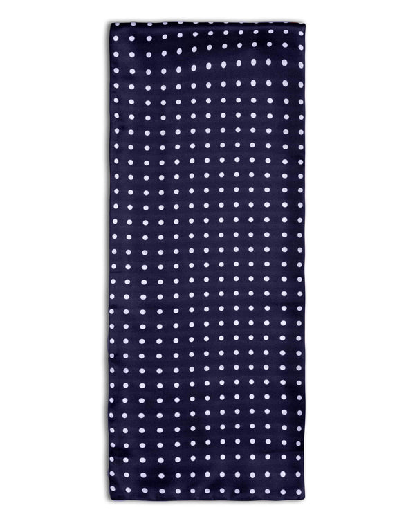 'The Westminster Silk' polka-dot scarf arranged in a rectangular shape, clearly showing the navy-blue fabric with white spots and the 'Soho Scarves' branding label on the bottom left edge.