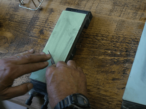 Whetstone being used to grind blades