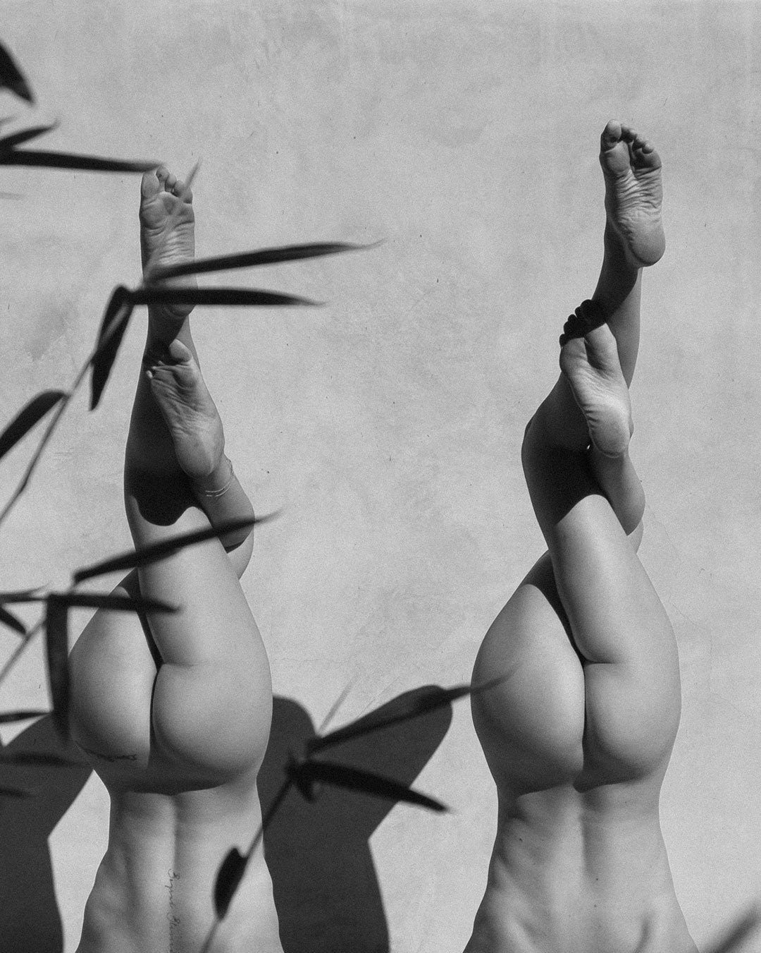 Two women performing a headstand eagle legs pose
