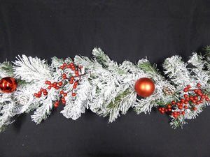 Artificial Christmas Garland with red berries, baubles and pine cone decorations on green snow dusted Fir.
