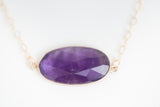 Amethyst stone set in gold bezel with gold chain