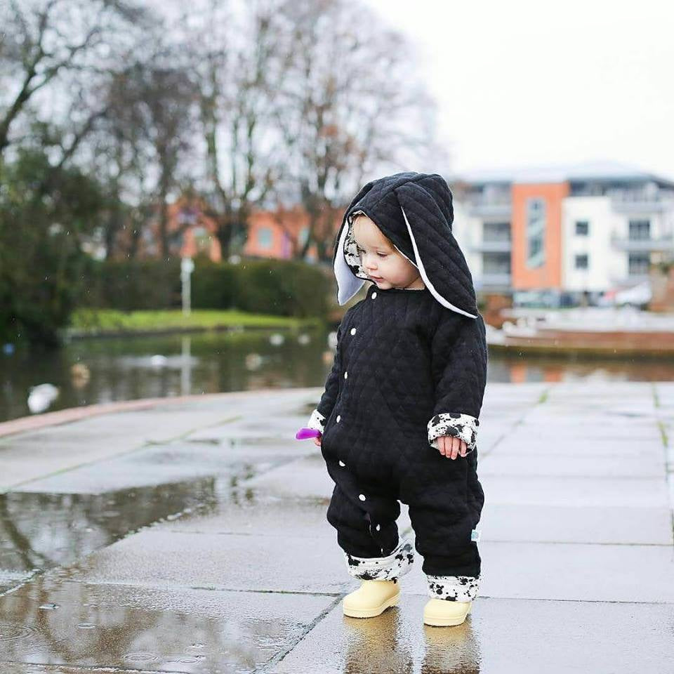 cute baby girl wearing lottie & lysh monochrome bunny pramsuit with splatter effect lining and yellow boots