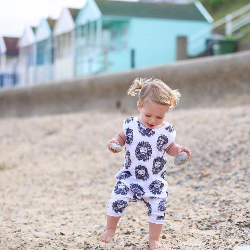 Toddler girl wearing Lottie & Lysh Aztec Lion organic romper on the beach with beach huts in the distance