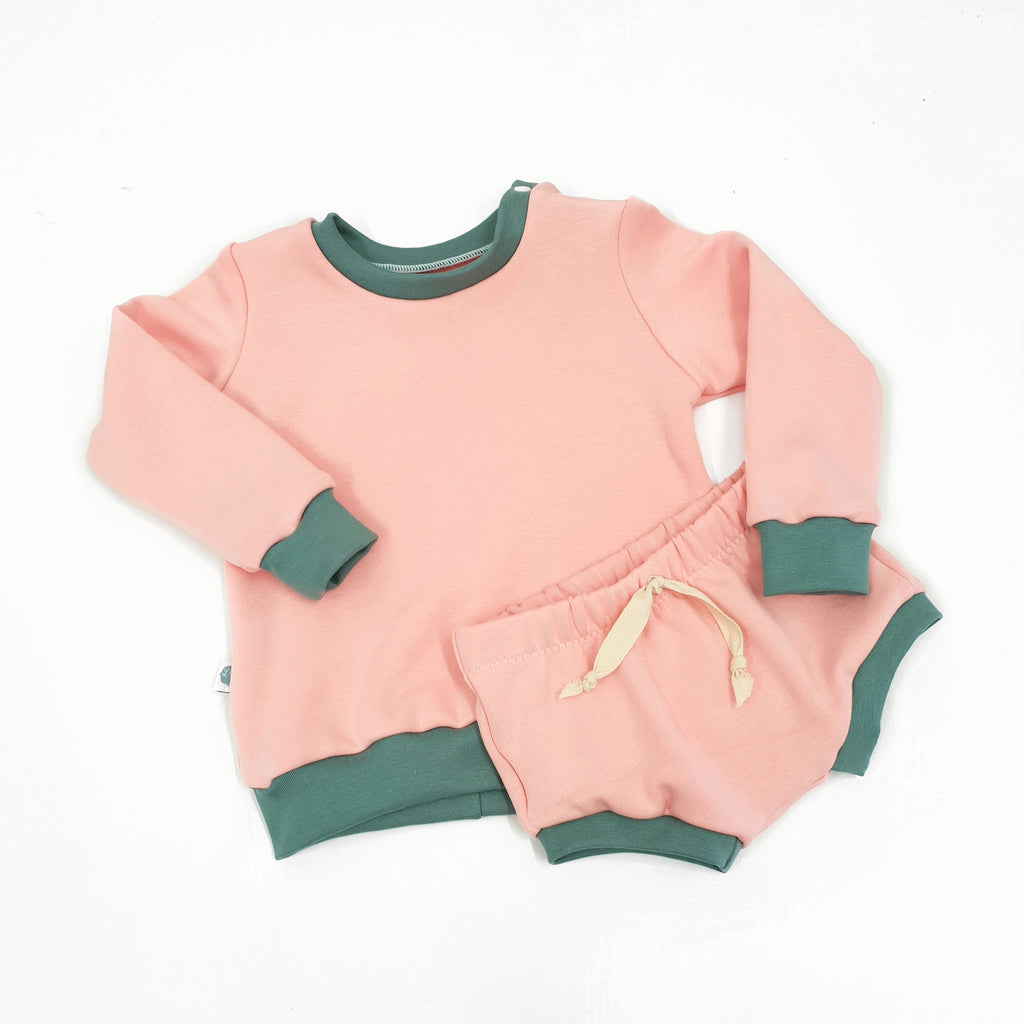 pink child and baby shorts with green trim and coordinating sweatshirt by lottie and lysh