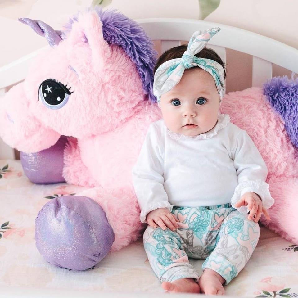 cute baby girl wearing lottie & lysh candy unicorn print leggings and matching headband set leaning against a large pink fluffy unicorn toy