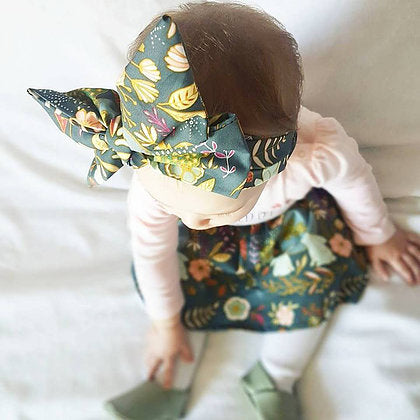 Baby girl wearing an floral skirt and big bow headwrap set