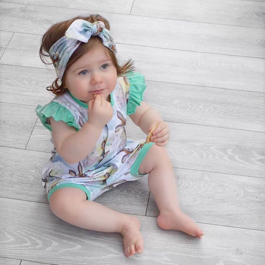 Baby girl wearing Lottie & Lysh Reggie frill shoulder bummie popper romper and matching headband