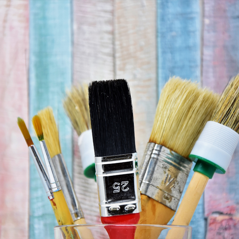 Decorative Garden fencing ideas - Paintbrushes in front of pastel painted fence