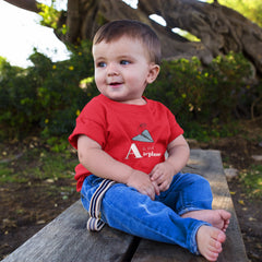 Smiling cute baby boy wearing a red one piece onesie with a blue origami airplane and the words A is for Airplane written in white font.  He is sitting on a bench that is outside in a shaded wooded area.
