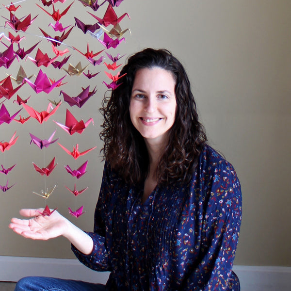 Debora is sitting next to a cascading spiral origami paper crane mobile. The cranes are made from papers in all different shades of red.