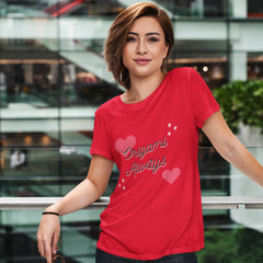 "Pretty smiling woman in a modern building wearing a red shirt that has origami hearts and the words ""Origami Always"" printed in black script."